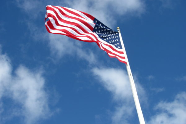 US flag waving in the wind against a blue sky